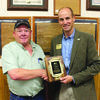 Before the main meeting, Craig Charles, senior vice president of retail sales, right, presented Mike Dawes, manager of Lockwood Farmers Exchange, a plaque to celebrate the Exchange's 95 years of service.
