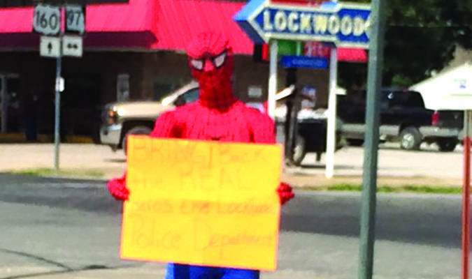 """A Lockwood resident voiced their opinion around noon Tuesday by dressing as Spiderman and standing near the 4-way stop in Lockwood with a  sign that reads """"Bring Back the REAL Hero's...the Lockwood Police Department."""""""