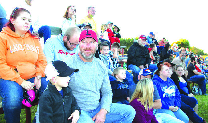 Roddric Onstott and his dad, Rodney, of Lamar, watch the tractor pull along with the crowd.