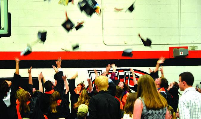 The graduates celebrate with a cap toss.