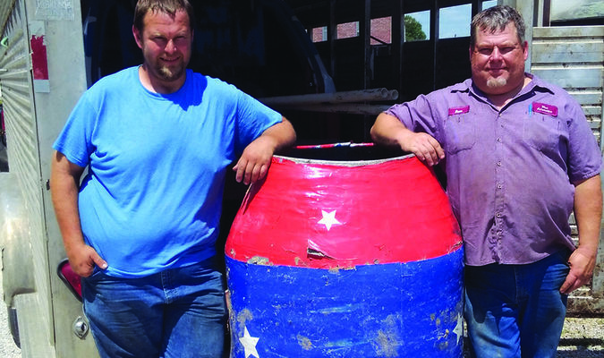 Casey Boyd, left and Dean Kimberling stand with the barrel that will protect them from the bulls.