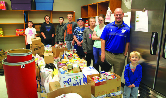 Greenfield students and Mr. Dobson with the food pantry donation inside at OACAC.