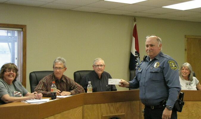 Greenfield Police Chief Tim Larkin presents a check for $100,000 received from the estate of Elsie Stephens during the April 7 meeting of the Greenfield Board of Aldermen. (Photo by James McNary)