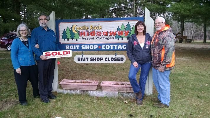 New owners Matthew Raw and Cindy Siefert-Raw hold the sold sign for Castle Rock Hideaway Resort with the former owners Steve Barbera and Jodi Jensen