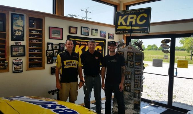 John Royer, front tire changer on the No. 20 Matt Kenseth NASCAR Sprint Cup Race Team recently visited Kluhsman Machine, where many of the parts found on pit row are made. Royer, left, is pictured with Mel Kluhsman, CEO of Kluhsman Machine and KRC Racing, center and Matt Osborn, engineer for Joe Gibbs Racing, right.