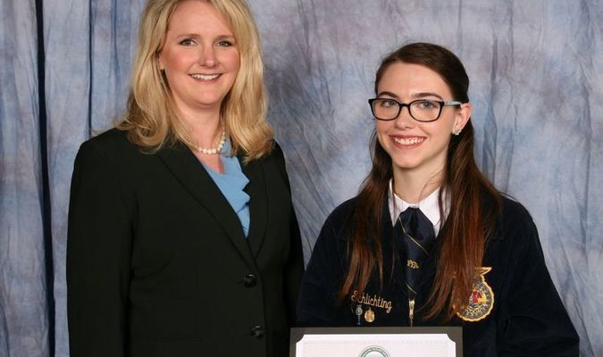 Missouri Department of Agriculture Director Chris Chinn, left, presents Megan Schlichting of the Lamar FFA Chapter with the Building Our American Communities Grant.