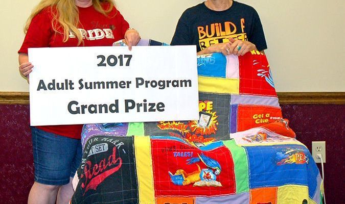 Lamar Democrat/Melody Metzger A Summer Reading Program quilt, made by Kristy Heckman, right, was presented to Teresa Shelton.