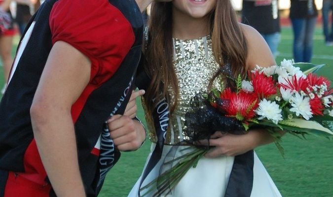 Lamar senior quarterback and 2017 homecoming king Stuart McKarus kisses the cheek of queen Darrah Bartlett prior to the Tigers route of McDonald County.