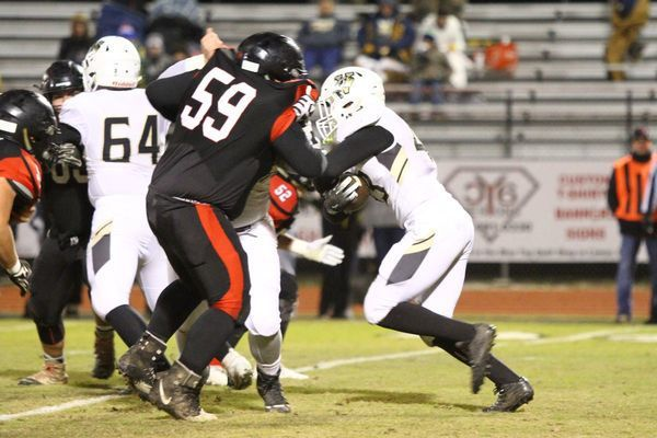 Photo courtesy of Terry Redman No. 59, junior lineman Carlos Paiz, tries to fight off a block to get to this Versailles running back. The Tigers defeated Versailles to advance to the quarterfinal game, where they hosted Ava on Saturday afternoon.