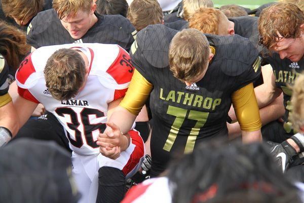 Lamar freshman No. 36 Stetson Wiss and a Lathrop player join hands as Duncan Gepner leads the teams in prayer. The Tigers have been asking the opposition to join them in a post game prayer since going to Valle Catholic almost three years ago.