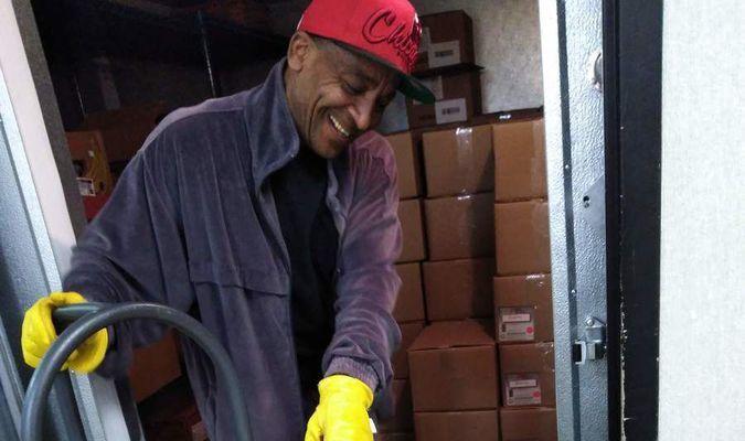 Sam McBride, a volunteer at Douglass Community Services, takes donated pork into the freezer.