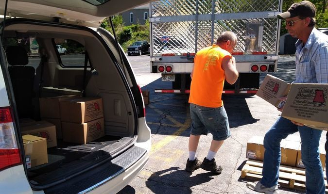 Brian Gaines, owner of Brian Gaines Trucking, helps load pork into a van headed to one of the area's agencies
