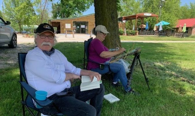 Two campers enjoy the outdoors under the shade, reading and painting in the Mark Twain Birthsite state park in city center of Florida Mo. while socially distancing. Photo by Warren Hagan M.D.