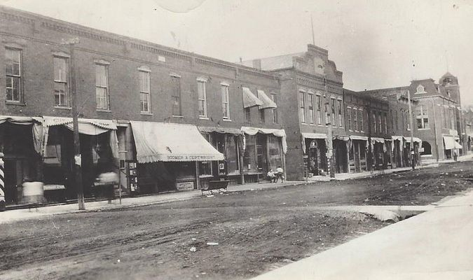 Photo shows in center of picture (tallest) is the where the extension office is now in 2019.  Notice the dirt streets!