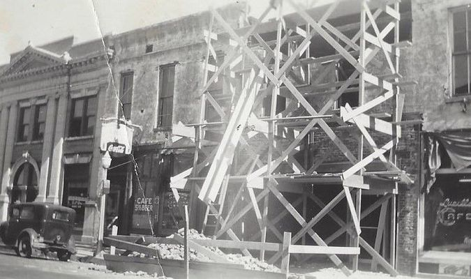 Photo shows the upper brick wall coming down and being replaced with the blonde brick that is there now in 2019 on this half block of buildings on East part of Main Street. Photo hows 1930 to 1940 car.