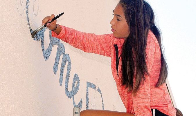 COMING ALONG: Marlow High School art student Alyssa Aguilera works on the lettering of the new mural going up at the intersection of Main and Broadway. All of the Marlow High School art classes are involved in the project.