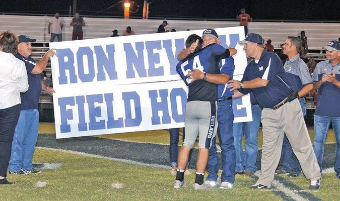 HONORED: Retired Marlow football coach Ron Newby receives a hug from his grandson, Brock Harris, during halftime of the Marlow and John Marshall football Friday night. The school district announced it was naming the football fieldhouse in Newby's honor.