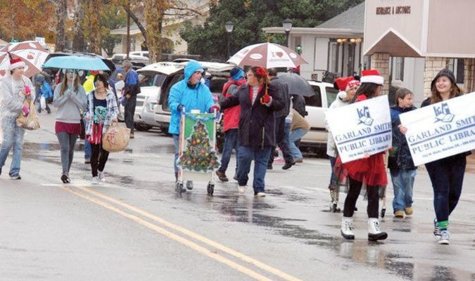 GETTING WET: Staff and volunteers from the Garland Smith Public Library walk along the Marlow parade route on Saturday morning. The weather conditions made attendance and participation smaller, but most people still seemed to enjoy themselves.