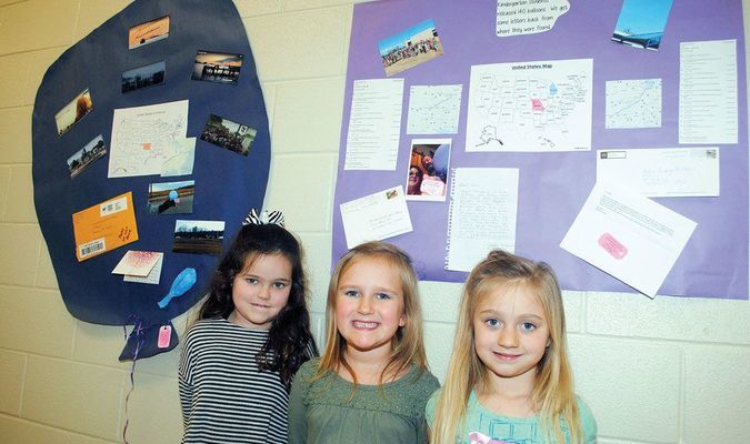BALLOON SUCCESS: Marlow Elementary School students Keira Blundell, Olive Bell, and Riley Gaskins stand beside displays of letters and photos of people in Michigan, Missouri, and Massachusetts who wrote letters to the kindergarteners after finding balloons they released on the 100th day of school.