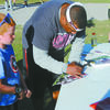 MEETING A SOONER: Ayden Pearson gets an autographed photo from former Oklahoma Sooner Jarrail Jackson at the Kaleb Pinson Co-Ed Softball Tournament last Saturday.