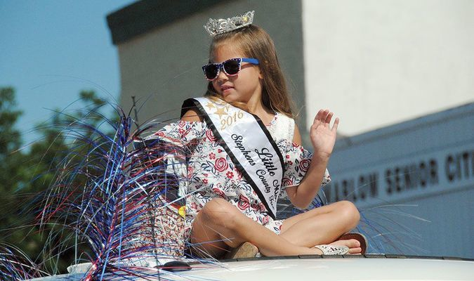 QUEEN CAB: Stephens County Free Fair Little Miss queen Addilen Wright sits atop a truck and waves to the crowd as part of the Marlow Fourth of July parade Tuesday.