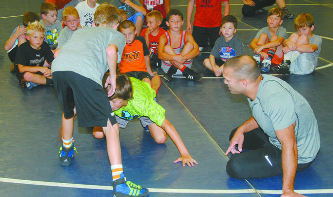 ALL THE RIGHT MOVES: Oklahoma State assistant wrestling coach Zac Esposito gives instructions on a takedown to elementary school wrestlers at the Rick Henshaw Memorial Stephens County Wrestling Camp in Marlow on Tuesday morning. The camp concludes today (Thursday) with a double-elimination tournament.