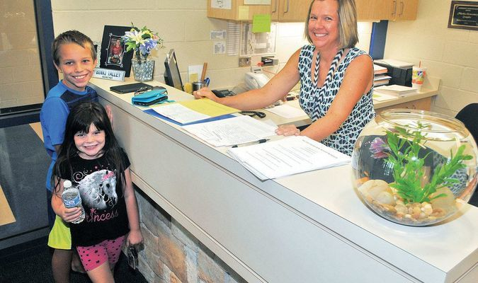 GETTING CLOSE: Jayden and Chevi-Lyn Rush were at Marlow Elementary School along with their mother to enroll for classes at Marlow Elementary School as MES secretary Leigh Throckmorton helps out on Tuesday morning. Classes begin at Marlow on Aug. 10.
