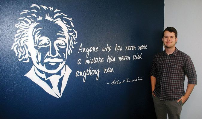 READY TO GET STARTED: New Marlow science teacher Taylor Schooling stands with a mural of Albert Einstein he and his wife painted for his high school classroom. It is one of two murals in the classroom.