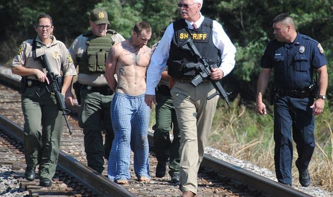 CAUGHT: Stephens County Sheriff Wayne McKinney leads a group of deputies and armed burglary suspect Andrew Dewayne Williams down railroad tracks following Williams' capture. A two-hour manhunt took place for Williams near the Ballpark Apartments in Marlow after he fled on foot to avoid an arrest warrant.