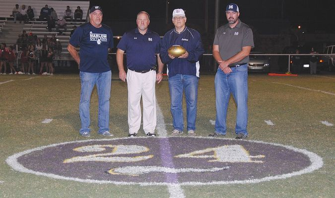 MARKING THE OCCASION: Former Minnesota Viking Terry Brown (second from right) presented a gold football commemorating Super Bowl 50 to Marlow athletic director Kirk Harris, superintendent George Coffman and high school principal George Coffman in 2015. Every player that had scored a touchdown in a Super Bowl got to present a gold ball to his high school alma mater. Brown scored in Super Bowl IX.