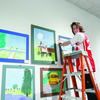 HANGING AROUND: Duncan High School senior and participating artist, Dalton Reid, hangs pieces in the Youth Art Month show at the Chisholm Trail Heritage Center. Reid installed the entire exhibit through his internship with the Heritage Center.