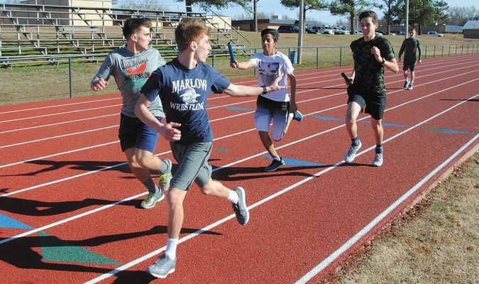 PASSING THE BATON: Marlow boys track team members practice handing off the baton for relay races Tuesday afternoon.