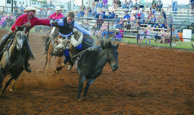 HELPING HAND: Mitchell Phillips gets an assist after a successful ride in the bucking bronc competition at last year's Duncan Noon Lions Club Rodeo. This year's rodeo will be held at Claud Gill Arena June 21-23.