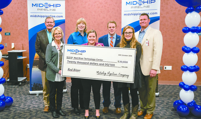 CHECK PRESENTATION: School and local officials celebrate receiving a $20,000 check from Midship Pipeline. Pictured: (front row, from left) Sylvia Loveday, Program Director; Laure Ferrell, Midship Pipeline Company; Kaitlyn Snider, Pre-engineering instructor; (back row) Sam Porter, School Board Member; Gretchen Taylor, Pre-engineering instructor; State Rep. Brad Boles; and Brook Holding, Deputy Superintendent, Red River Technology Center