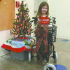 THINKING OF OTHERS: Kara Poplin stands with the walker she purchased for her Uncle Ronnie Shipman at the Santa Shop, a PTO fundraiser, after telling her aunt she wanted to spend her money on him, not herself.