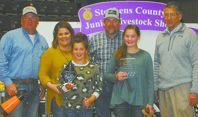 NEAR-PERFECT DAY: Sisters Emma and Avery Throckmorton received several high honors during the opening day of the Stephens County Junior Livestock Show on Tuesday. Pictured with Emma's grand champion gilt are: (from left) Wes Phillips, Nicole Throckmorton, Avery Throckmorton, Brady Throckmorton, Emma Throckmorton and swine judge Rex Smith.