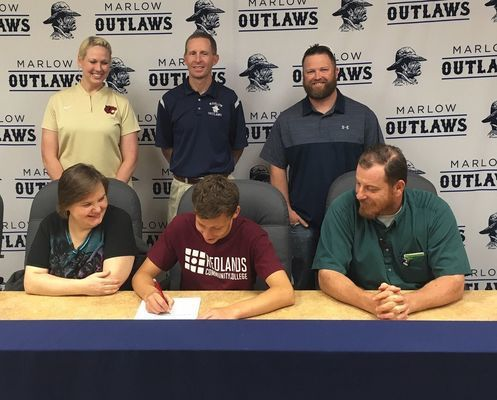 Andrew Brown signs a Letter of Intent while his family and coaches look on. Front row: Stacy Brown, Andrew Brown, James Brown. Back row: Redlands Cross Country Head Coach Natalie Cox, Marlow Cross Country Assistant Coach Matt Ivory, Marlow Cross Country Head Coach Mikey Eaves. Photo Submitted