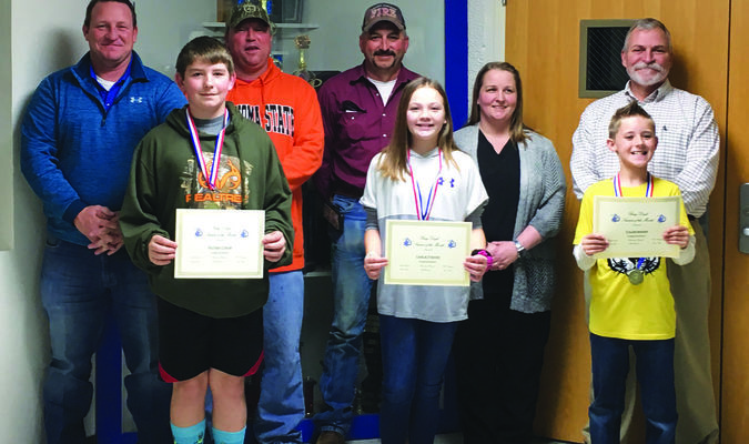 Bray-Doyle Students of the Month Rayden Crow, Carlie Foster, and Caleb Baker pose with members of the school board and superintendent David Eads.