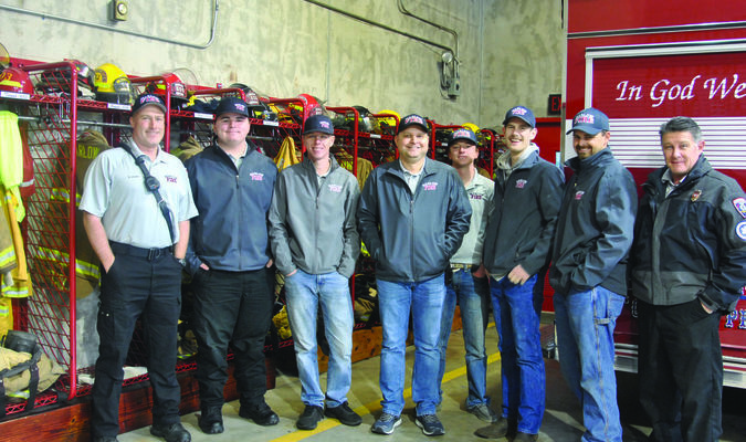 A Place for Everything: Firefighters Shane Linam, Jakob Herriage, Alex Barker, Adam James, Dayton O'Neal, James Bourke, Eric Spurlock, and Michael Pope show off new gear racks that were recently installed thanks to a gift from an anonymous donor.  Photo by Elizabeth Pitts-Hibbard
