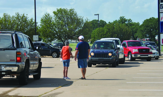 Reaching out to families: Volunteer Robert Newman gives directions at the Farmers to Fami-lies food distribution on Monday. Dozens of residents arrived early for the distribution, lining up in the parking lot at 4303 N. Highway 81. Photo by Elizabeth Pitts-Hibbard