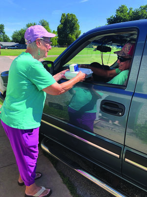 """Nellie Carr, a volunteer with Marlow Senior Nutrition, delivers lunch to one of her """"regulars"""" at the Redbud Community Center. Carr has worked every weekday at the Center since March 17,  serving drive-up meals to senior citizens in the area."""