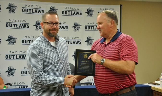 Darren Alaniz (left) receives a plaque from Marlow Public Schools Superintendent George Coffman in appreciation for his service to the Marlow Board of Education at Tuesday's board meeting. Alaniz announced his resignation from the board after eight years of service.  Photo by Elizabeth Pitts-Hibbard/The Marlow Review