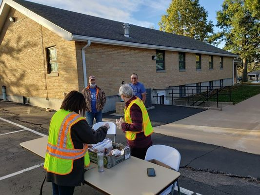 Pictured are Fr. John Henderson and Cassie Gonzalez with St. Williams parish at the table and in the back are Rick Ellison and Lamar Utterback.