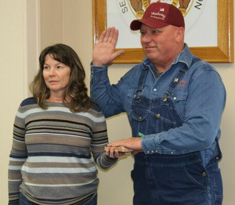 Junior Muehring is sworn in as Eastern District Commissioner with his wife Jenni holding a bible that went to Vietnam with Bill Dexheimer, who gave it to Junior's daughter Heather, when she went to Iraq.