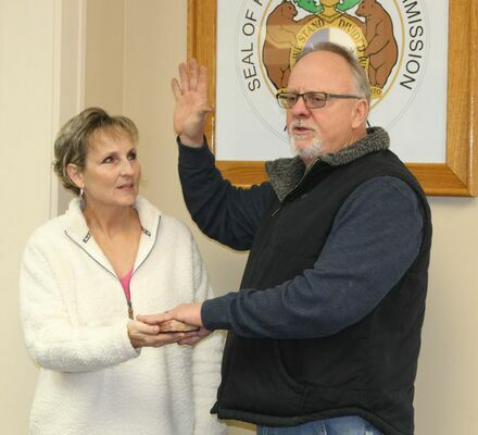 John Lake, re-elected Western District Commissioner, is sworn in with his wife, Sharon, holding the bible.