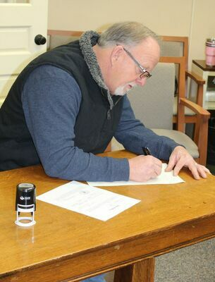 Western District Commissioner, John Lake completes paperwork after being sworn in.