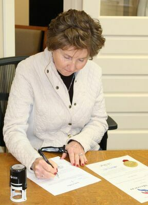Public Administrator, Paula Evans, signs the required paperwork at her swearing-in.