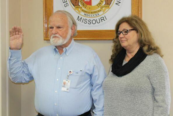 Re-elected Coroner, Robert Van Winkle, is sworn in with him wife Judi looking on.