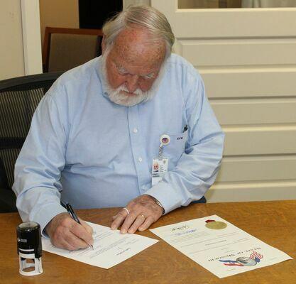 Signing paperwork after being sworn in is Robert Van Winkle.
