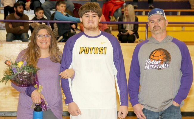 BRYCE REED, #55 for the Trojans, was joined by his mom and dad, Paulette and Justin Reed on the court. Reed plans on bowling at Lindenwood College and studying in the Pre Vet Program.